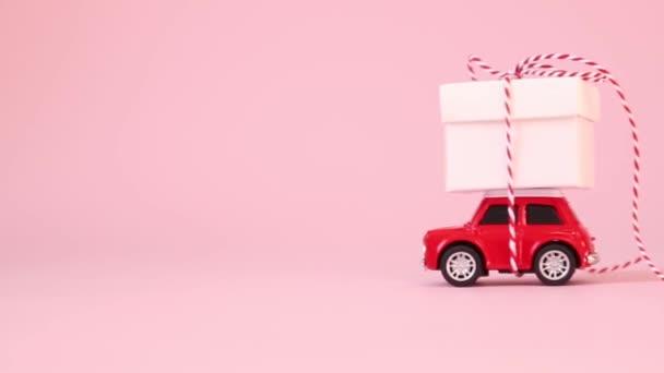 Červená dodávka autíčka dárková krabice s mašlí luk na růžovém pozadí. Narozeniny, Valentýn, Dámský den koncept.