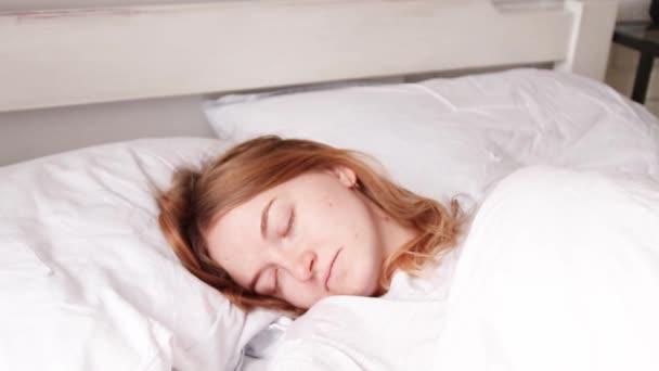 Mladá blondýnka spí v posteli. Koncept snu