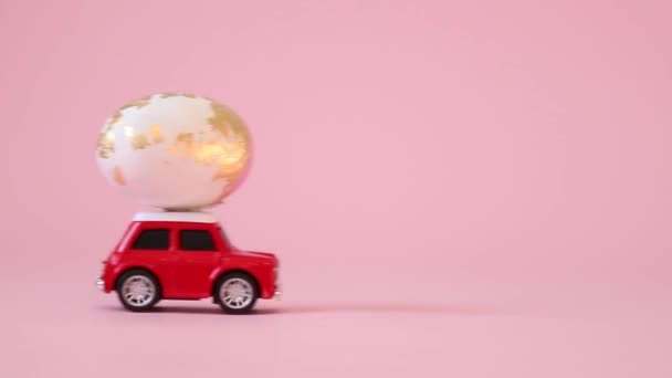 Little red toy car with a golden egg on the hood on a pink background. Gift delivery. Happy easter concept