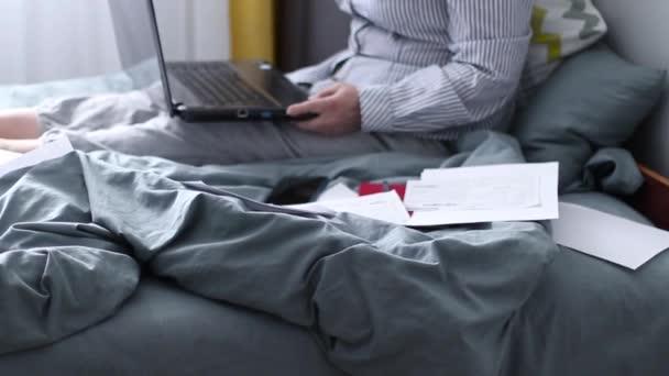 Dospělá žena s laptopem sedící na posteli v domácí kanceláři. Platba účtů
