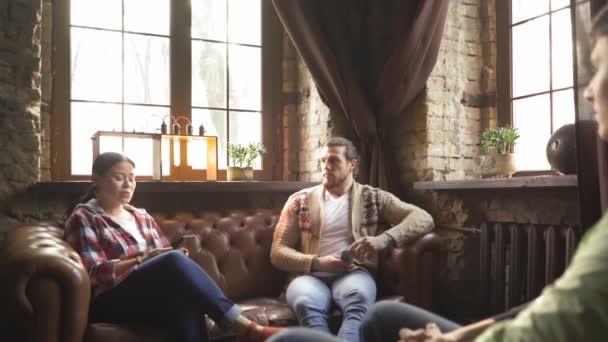 Multiethnische Gruppe von drei Männern und Frauen, die auf einer Couch in einem modernen Büro sitzen. Mittleres Alter asiatische Frau sitzt mit freien Mitarbeitern auf einem Ledersofa. Studenten treffen ihren Kurator