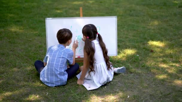 Rear view Young students are sitting on the street on the green grass and fresh air and are drawing or studying arithmetic using a white board.