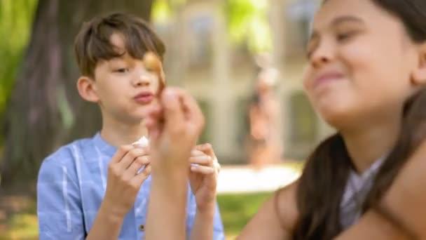 Két gyerek kint ül az iskola előtt, szendvicset esznek.