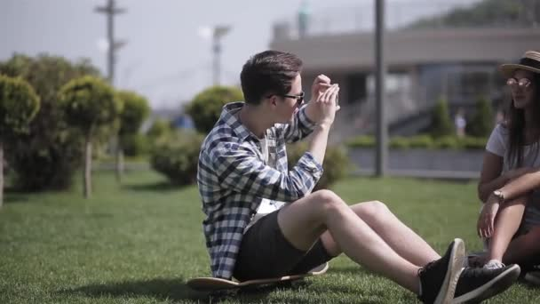 Friends tourists spend time together in a new city and take photos while sitting on grass at the city background. A friend takes a photo of a couple against the backdrop of the city. Prores 422
