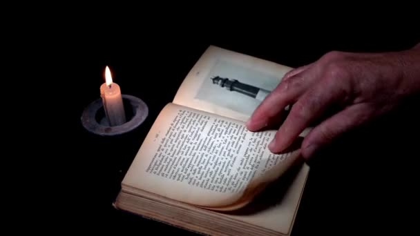 puffed book by candlelight on black. Vintage and traditional effect. In the end, the reader puts down his glasses.