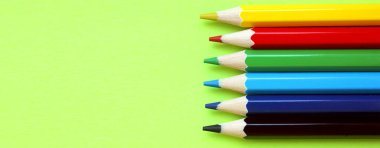 Colored pencils on a yellow background. 6 colors Black, blue, blue, green, red, yellow. Pencils are well-honed. Flatlay. Isolated. Art. Art therapy. Leisure. Pencils are placed on the right. Banner