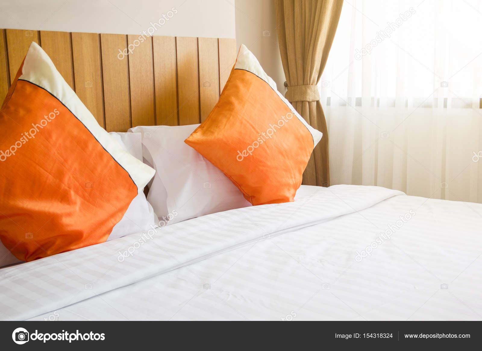 Cuscino arancione e bianco coperta sul letto nella camera da letto