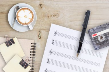 Sheet music, fountain pen, tape cassette and coffee latte on wooden table, top view picturele, top view picture