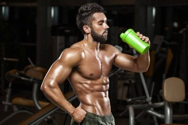 Sexy muscular man drinking water in gym, shaped abdominal. Strong male naked torso abs, working out