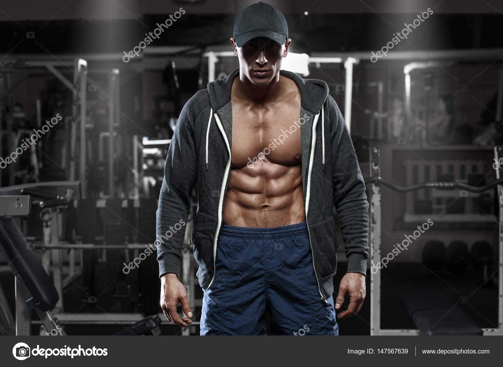 Muscular Man With Open Jacket Revealing Chest And Abs In Gym Workout Stock Photo