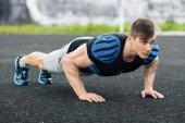 Uomo di forma fisica facendo flessioni nello stadio, Croce allenamento training. Tempo libero attivo maschio di addestramento