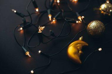 Golden Christmas decorations on black background.