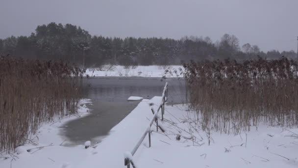 Der nicht gefrorene Fluss fließt im Winter. Badesteg Brücke Schnee, Wald und Tauwetter
