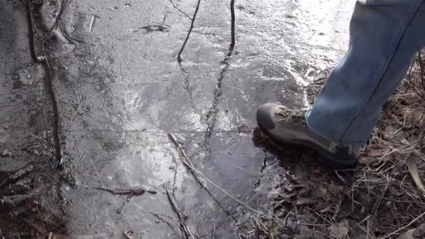 Der Mensch berührt das dünne Eis und betritt es. Herbst oder Frühling. Eisbruch.