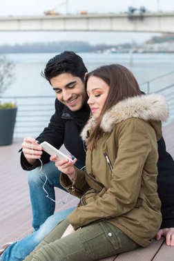 Man and woman looking at mobile phone on street