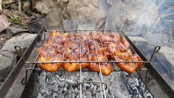 Grillcsirkeszárnyakat grillsütőn tűzlángokkal és füsttel. Szelektív fókusz. Nyári kaja. Barbecue ötletek, grill party, bbq.