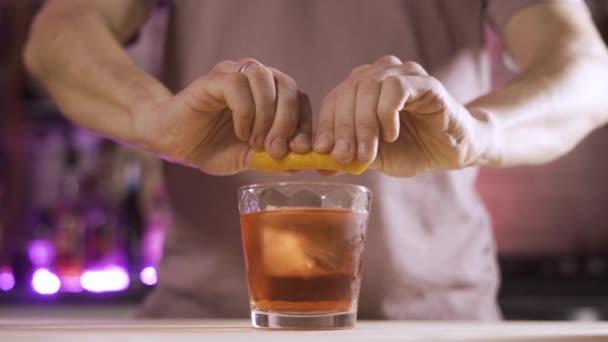 barman vymačkává oranžovou kůrku do sklenice s černošským koktejlem