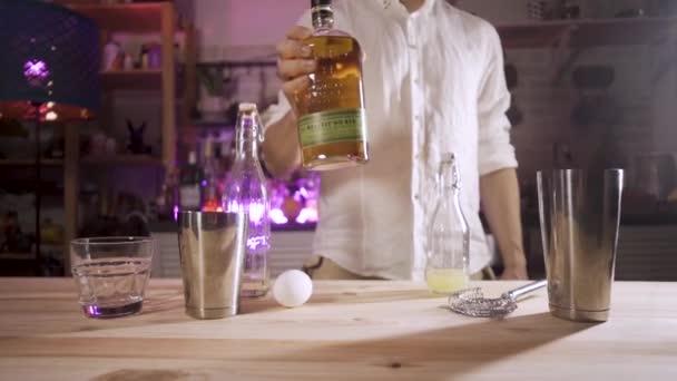 Barman zvedne láhev whisky a položí ji na stůl před kameru. Kamera sleduje objekt