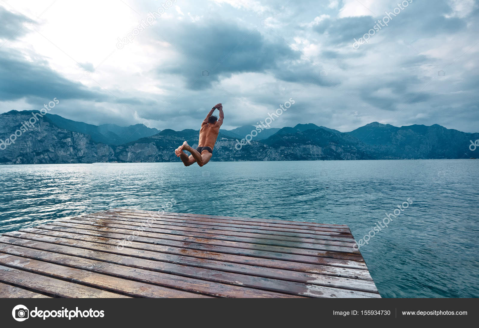 Man jumping into the water from the pier — Stock Photo