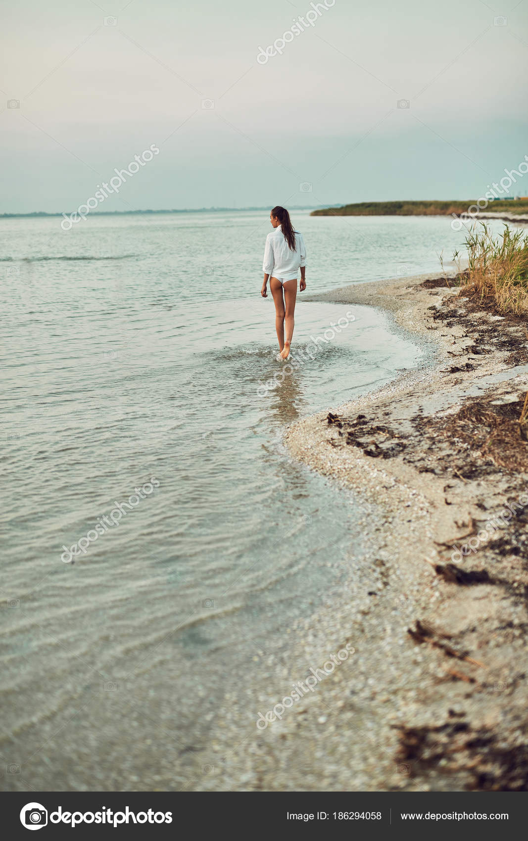 Beautiful sexual woman in white shirt and bikini walking on the beach  against the sea and sunset. happy woman enjoying summer vacation — Photo by  ...
