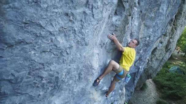vide úhel pohled na člověka horolezec ve žlutém tričku, šplhání na útes, hledání, sahání a uchopení. outdoors horolezectví a aktivní životní styl koncept