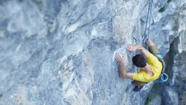 vide angle view of man rock climber, climbing sport route on a cliff, searching, reaching and gripping hold, resting and chalking hands