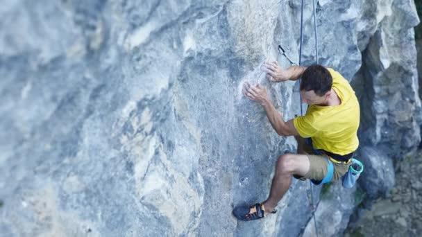 shora pohled na člověka horolezec, horolezectví sportovní trasa na útesu, hledání, sahání a uchopení úchyty. venkovní rock