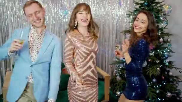 Fröhlich feixende Menschen tanzen mit Sektgläsern auf der Weihnachtsfeier.