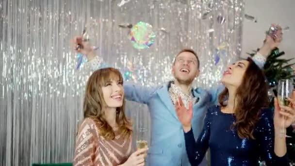két gyönyörű csodálatos lányok divatos fényes ruhák és stílusos férfi ünnepli újév, születésnap és tartja poharak pezsgő.