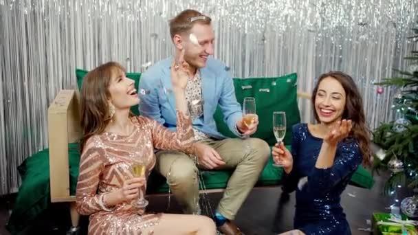 lassított felvétel két gyönyörű csodálatos lány divatos fényes ruhák és stílusos férfi ünnepli újév, születésnap és tartja poharak pezsgő.