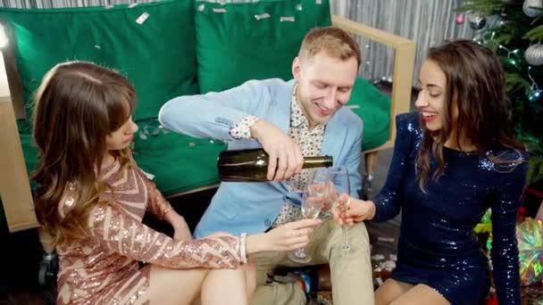 junger stilvoller Mann gießt Champagner in Gläser auf Party für zwei schöne Frauen und verschüttet Wein an einem Glas vorbei.
