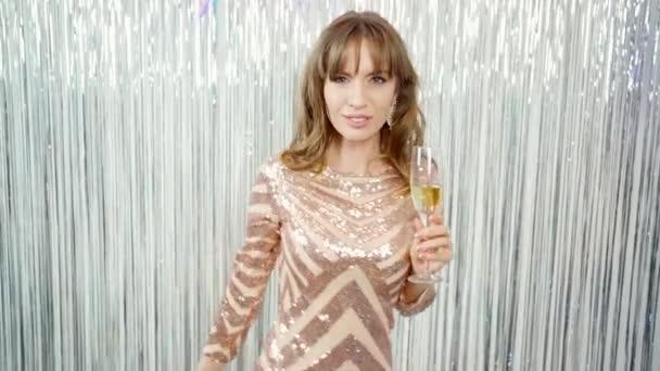 boldog mosolygós játékos gyönyörű fiatal nő pezsgős pohár ünnepli az új évet, és játékosan néz a kamerába