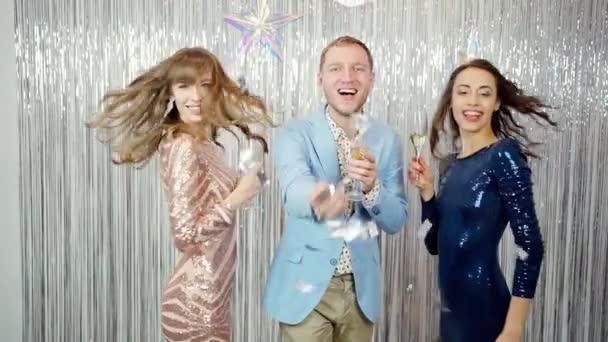 Portré a fiatal férfi és két csodálatos gyönyörű nők divatos fényes ruhák paillette ünneplő újév, születésnap és tartja üveg pezsgő