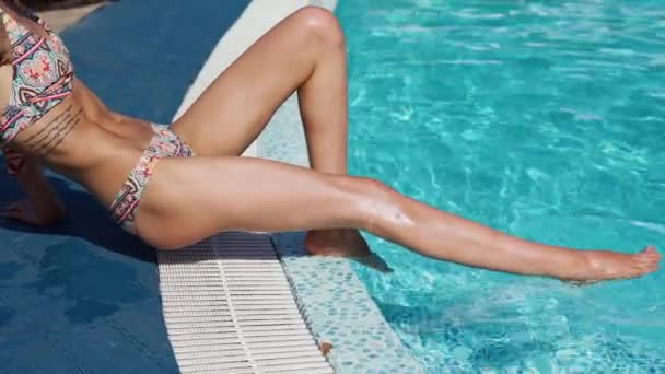 Young slender sexy tanned woman splashing water with legs sitting by pool