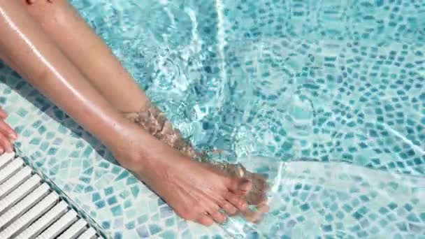 top view legs of unrecognizable woman relaxing, sitting in swimming pool at luxury hotel spa