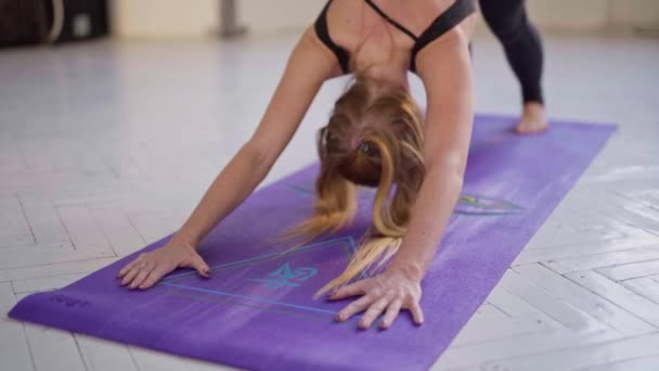 hajlékony fitnesznő fekete sportruházatban jógázik, lefelé néző kutyapózban áll, Urdhva mukha shvanasana