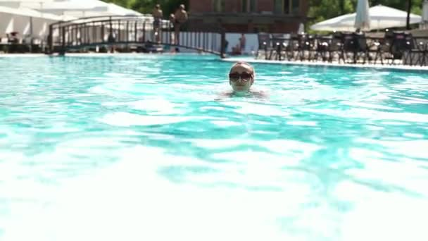 beautiful young woman in sunglasses swimming and comes up on pool edge by hands and joyfully looking at camera.