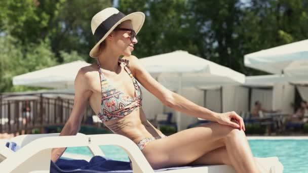 beautiful Caucasian bikini girl in hat sitting at pool edge on desk chair and sunbathing.