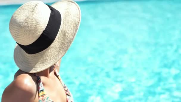 closeup beautiful Caucasian girl in hat sitting at pool edge on clear blue water background and sunbathing.