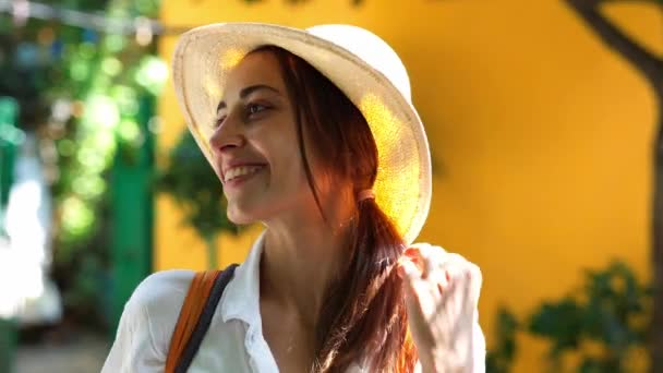 Portrait beautiful tourist woman in straw hat, white shirt smiling to camera, standing against bright orange wall in tourists city.