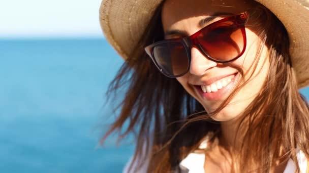 közelkép bájos mosolygós nő utazó szalma kalap és napszemüveg séta a tengerparton a napsütéses napon