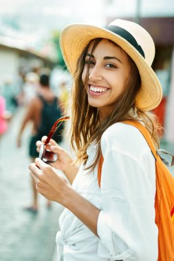 Closeup portrait joyful woman tourist in straw hat and white shirt looking to camera wiht smile.