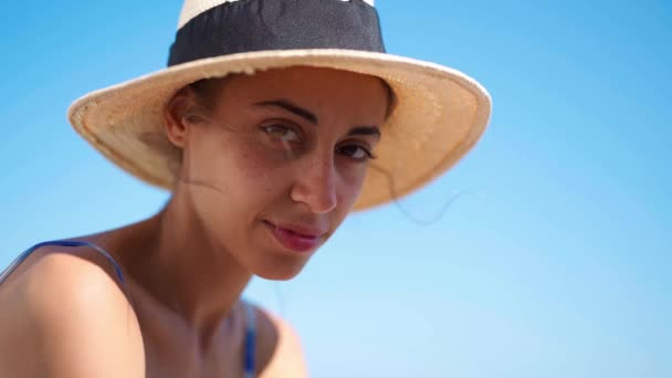 slow motion close up portrait young woman in straw hat on background of blue sky
