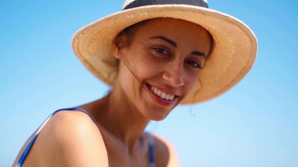 detailní tvář krásné opálené ženy v slamáku klobouk na pozadí modré oblohy.