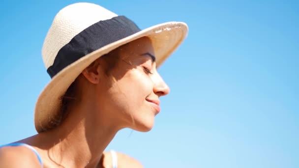 profil kilátás gyönyörű nyugodt nő szalma kalap élvezi a nap és a meleg napfény.