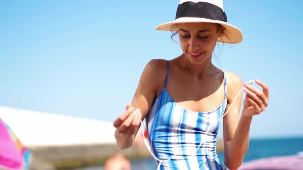 beautiful tanned woman in swimwear and straw hat taking earphones and listening music from phone