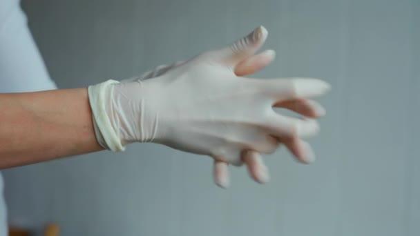 Arzt auf Krankenhausstation zieht sterile Schutzhandschuhe auf weißem Hintergrund an