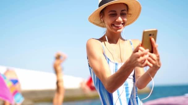 joyful krásná dívka v plavkách a klobouku dělat selfie nebo video chat
