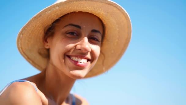 usmívá mladá nezávislá sebevědomá žena v klobouku na pozadí modré oblohy