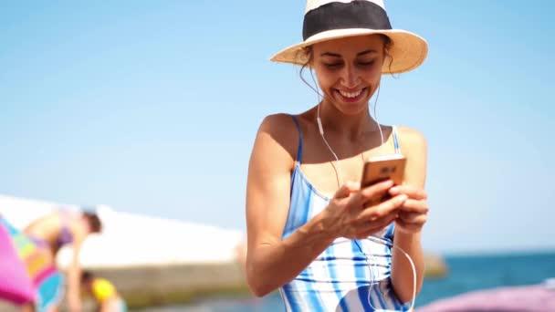 fiatal cserzett nő csíkos fürdőruhában és szalmakalapban, fülhallgatóval és telefonnal zenéléshez